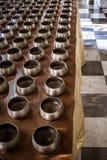 La rangée de l'aumône argentée roule avec de petites pièces de monnaie à l'intérieur dans le temple bouddhiste image stock