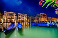 La rangée de pilier de gondole de canal grand de l'Italie Venise ancrée du jour au lendemain au coucher du soleil a brouillé illu Photos stock
