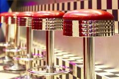 La rangée de vintage des tabourets de bar en métal, intérieur, métal rouge préside près photographie stock