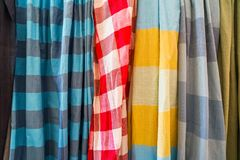 La rangée des écharpes molles colorées traditionnelles de tissu de coton en plaine et le contrôleur modèlent la vente dans la bou photographie stock