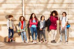 La rangée des adolescents avec des planches à roulettes et fait du roller Photos libres de droits