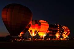 La rangée des ballons à air chauds allument le ciel pendant une lueur de ballon Photos stock