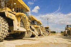La rangée des camions de déchargeur garés dans le parc à bestiaux d'un ciment fonctionne le R-U Image stock