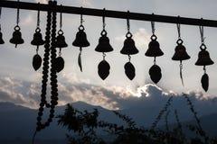 La rangée des cloches et le chapelet dans le coucher du soleil s'allument Images libres de droits
