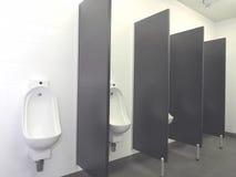 La rangée des cuvettes d'urinoir avec les mains automatiques libèrent à affleurement dans des toilettes industrielles immaculées Photo stock