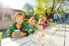 La rangée des enfants se reposent ensemble à la table blanche en bois Photos libres de droits