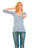 La rappresentazione teenager sorridente della ragazza se lo mette in contatto con gesto fotografia stock