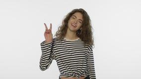 La rappresentazione v della giovane donna firma in studio Segno di vittoria di rappresentazione della ragazza del vincitore archivi video