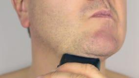 La rasatura del primo piano un uomo, rade il rasoio elettrico, in primo luogo video d archivio