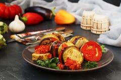 La ratatouille è situata su un piatto su un fondo scuro Verdure al forno: melanzane, zucchini e pomodori immagine stock libera da diritti