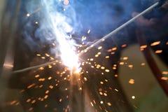 La reacción del alambre de soldadura y el metal con humo encienden y chispean Imagenes de archivo