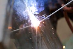 La reacción del alambre de soldadura y el metal con humo encienden y chispean Fotos de archivo