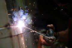 La reacción del alambre de soldadura y el metal con humo encienden y chispean Imagen de archivo