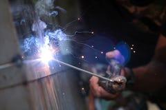 La reacción del alambre de soldadura y el metal con humo encienden y chispean Imágenes de archivo libres de regalías