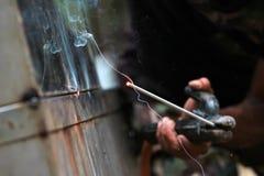 La reacción del alambre de soldadura y el metal con humo encienden y chispean Imagen de archivo libre de regalías
