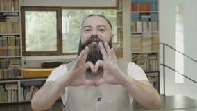 La reazione di flirt di giovane uomo attraente con la barba che fa un cuore modella facendo uso delle sue mani e dita - stock footage