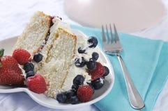 La rebanada de crema azotada fresca y las bayas acodan la torta de esponja Imagenes de archivo