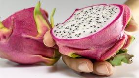 La rebanada de dragón da fruto en las frutas sanas de la mano Foto de archivo