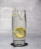 La rebanada de limón cayó en el vidrio de agua Imagen de archivo libre de regalías