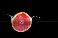 La rebanada fresca del pomelo cayó en el agua Foto de archivo libre de regalías