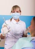 La recepción estaba en el dentista de sexo femenino que Doctor examina la cavidad bucal en caries Imágenes de archivo libres de regalías