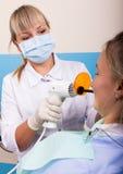 La recepción estaba en el dentista de sexo femenino que Doctor examina la cavidad bucal en caries Imagen de archivo libre de regalías