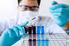 La recherche de laboratoire de biochimie, chimiste analyse l'échantillon dans le laboratoire avec l'équipement et la verrerie d'e photographie stock libre de droits