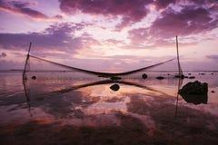 La red de pesca se refleja en el agua en la puesta del sol fotos de archivo libres de regalías