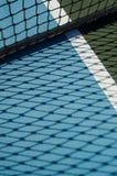 La red del campo de tenis echa la sombra en la tierra azul foto de archivo