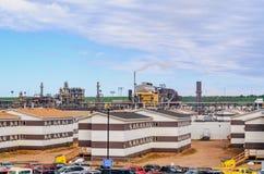 La refinería de petróleo canadiense más grande del fondo, parqueando en el primero plano, tubos que fuman Imagen de archivo