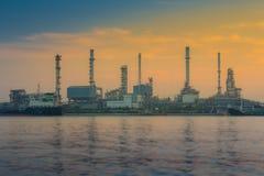 La refinería de petróleo reflejó en el río durante tiempo de la salida del sol Imagenes de archivo