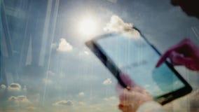 La reflexión de Defocussed de un hombre que usaba una tableta hizo excursionismo por el sol almacen de metraje de vídeo