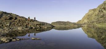 La reflexión de dos individuos que caminan a través de las montañas Fotos de archivo libres de regalías
