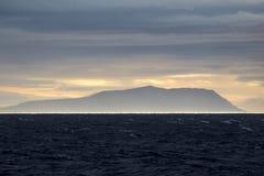 La reflexión de Sun en el mar en Svalbard, Noruega con el fondo de la montaña fotografía de archivo