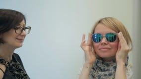 La reflexión en blonde del espejo, lleva las gafas de sol, estilista moreno ayuda almacen de video