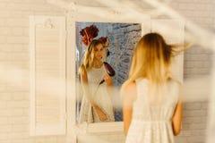 La reflexión en el espejo moderno del adolescente que seca el pelo Imagenes de archivo