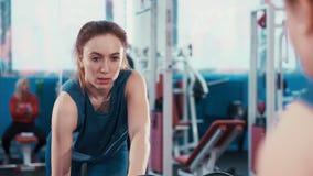 La reflexión en la muchacha joven de la aptitud del espejo realiza un ejercicio con una pesa de gimnasia almacen de video