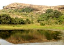 La reflexión hermosa de la colina en la piscina en el complejo sittanavasal del templo de la cueva Foto de archivo libre de regalías
