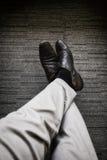 La refrigerazione di rilassamento del giovane di affari con le gambe ha attraversato su tappeto immagini stock