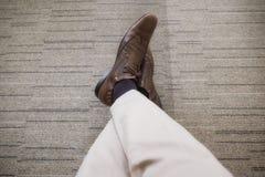 La refrigerazione di rilassamento del giovane di affari con le gambe ha attraversato su tappeto immagini stock libere da diritti