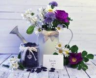 La regadera del vintage con las rosas salvajes, le ama baya del texto y de la madreselva en tarro Fotografía de archivo