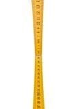 La regla de plegamiento aislada, regla amarilla del ` s del carpintero con centímetros numera Foto de archivo