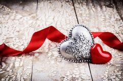 La regolazione del biglietto di S. Valentino con i cuori decorativi ed il nastro rosso Immagini Stock