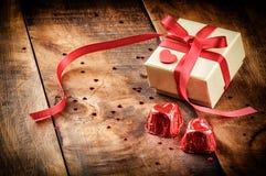 La regolazione del biglietto di S. Valentino con il contenitore ed il cioccolato di regalo Immagine Stock