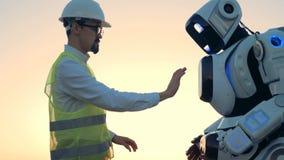 la regolazione del robot del tipo di umana sta regolanda da un ingegnere in un elmetto protettivo video d archivio