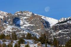 La regolazione della luna dietro i picchi di montagna nevosi in Rocky Mountain National Park immagine stock libera da diritti