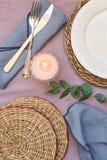 La regolazione vuota della tavola, il piatto elegante e bianco, sottobicchieri del rattan, ha acceso la candela, la coltelleria,  Fotografie Stock Libere da Diritti