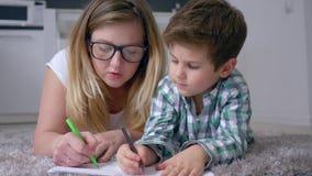 la relación del Madre-niño, femenina con el muchacho con los lápices coloreados dibuja imágenes en la hoja que miente en piso en  almacen de video