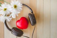 La relaxation et confortables avec le coeur écoutent musique et marguerite sur en bois Photo stock