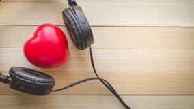 La relaxation et confortables avec le coeur écoutent musique sur le fond en bois Images libres de droits
